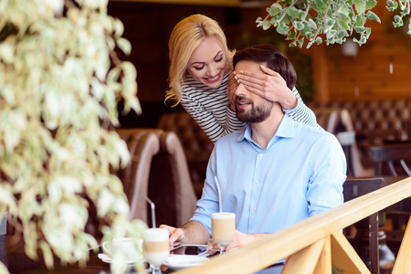 guess: Guess who it is. Carefree young woman is covering male eyes secretly. She is standing and smiling. Man is sitting at table in restaurant