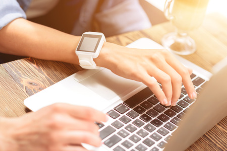 cropped shots: They are always in touch. Cropped shot of woman sitting at cafe and wearing smartwatch, using laptop with her friend