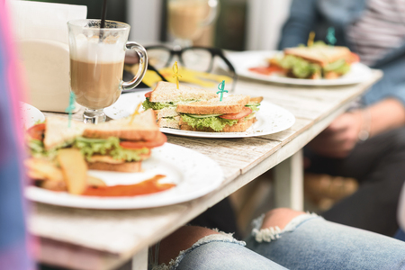 Consumables: Goodbye diet. Close up of tasty sandwich on plate on table near latte with people in background Stock Photo