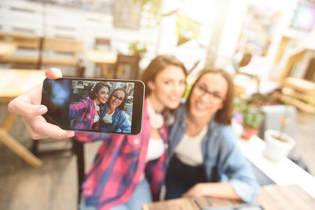 hang out: All smiles when friends hang out. Shot of two girlfriends taking selfie on mobile phone, sitting in coffee shop Stock Photo