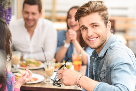 adult sandwich: All together again. Smiling positive guy sitting in cafe with friends and enjoying conversations with them Stock Photo