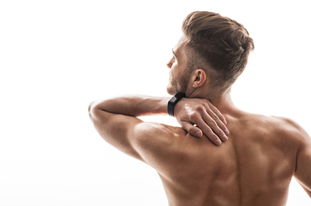 back sprains: Young man suffers from ache. He is touching neck with despair. Athlete is standing and showing back. Isolated and copy space in left side