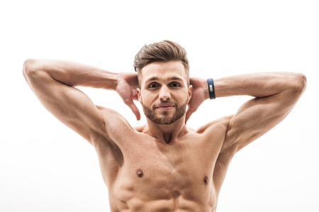 arms behind head: Strong young sportsman is training his body. He is raising arms behind head and smiling. Isolated