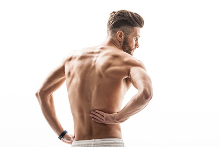 desperation: Fit man suffers from pain. He is touching his back with desperation. Isolated