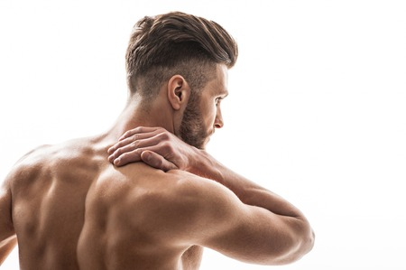 back sprains: Young athlete is massaging his neck with pain. He is standing with bare back and looking forward with frustration. Isolated and copy space in right side Stock Photo