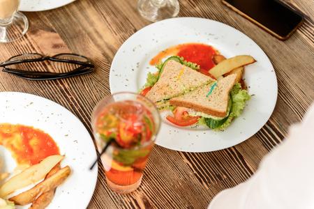 Almuerzo de domingo. Cerca de sabroso sándwich con tomates, ensalada y pepino en plato blanco de pie en la mesa de madera en café