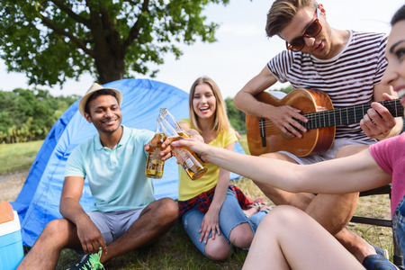 near beer: Cheers. Carefree men and women are clinking bottles of beer. They are sitting near tent and laughing. Young guy is playing guitar and singing