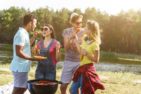 Joyful friends are resting in the nature. Men are feeding women with barbecue. They are standing near grill and laughing Stok Fotoğraf