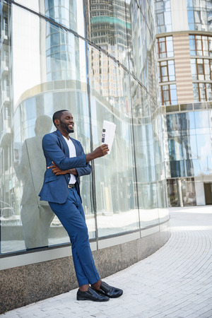 article of clothing: Carefree African man is reading newspaper with interest. He is leaning on wall of building with relaxation. Worker is standing and smiling
