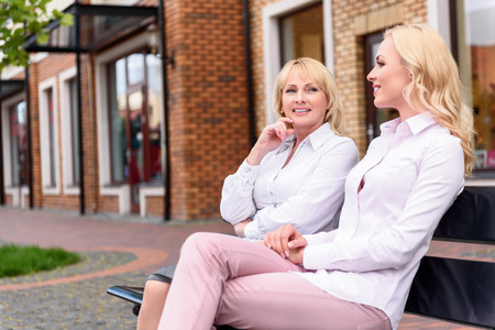 mother on bench: Mother and daughter resting outdoors together. They are sitting on bench and talking. Women are smiling