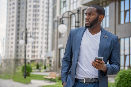 seriousness: Confident African businessman is waiting for meeting in city. He is standing and looking aside with seriousness. Man is holding smartphone Stock Photo