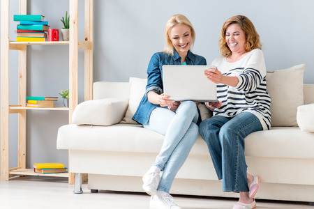 they are watching: Happy mother and daughter are watching movie on laptop and laughing. They are sitting on sofa at home Stock Photo