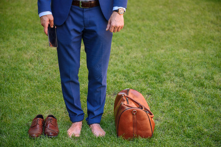 barefoot man: Close up of male legs standing on grass barefoot. Man is holding mobile phone. There are his bag and shoes on lawn