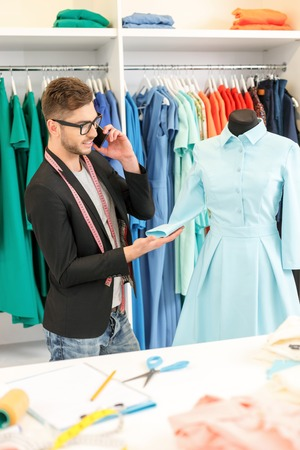atelier: Cheerful young tailor is working in atelier. He is talking on mobile phone and smiling. Man is standing and touching dress on mannequin
