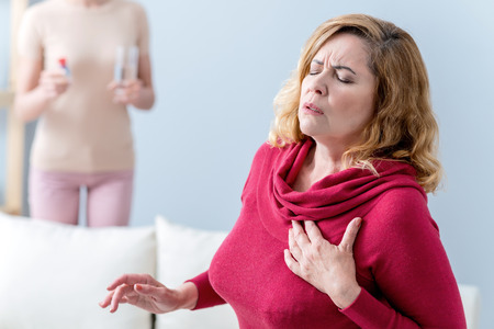 Senior woman feels terrible pain in heart. She is touching her chest with frustration. Her daughter is standing with pills and water on background