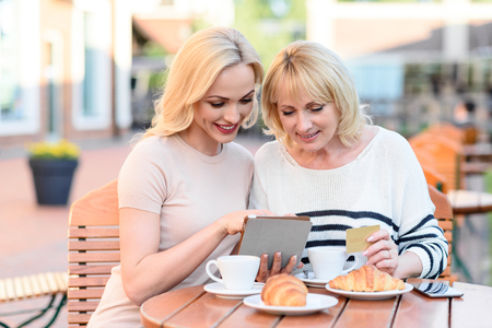 family and friends: Online shopping. Cheerful mother and daughter are using tablet and smiling. They are sitting at table in cafe. Senior woman is holding credit card