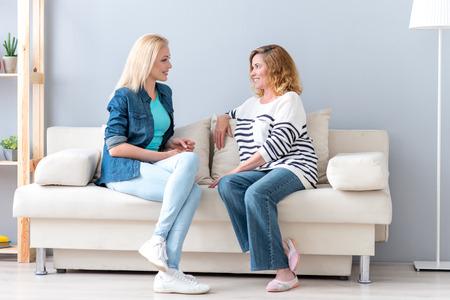 La madre e la figlia graziose stanno godendo il colloquio amichevole a casa. Sono seduti sul divano e sorridenti