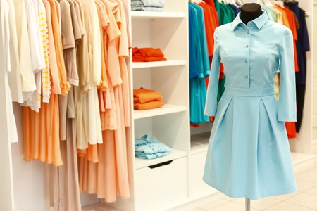 Fashionable designer dress on mannequin near clothes on hangers in boutique Banque d'images
