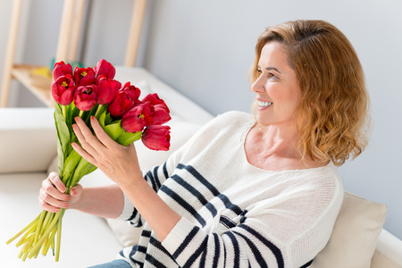 appreciating: Happy mature woman is receiving bouquet of tulips with pleasure. She is sitting on sofa and smiling