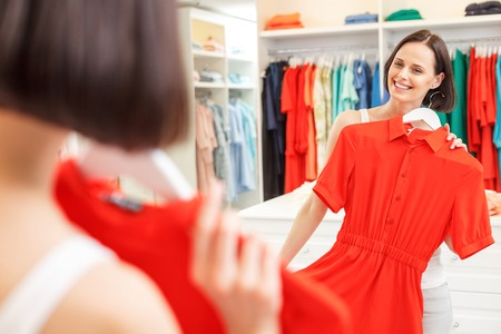 red cloth: Beautiful young girl is trying on red dress in shop. She is standing and looking at mirror with pleasure. Woman is smiling happily