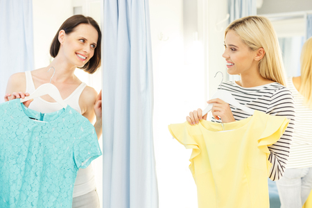 changing room: Two women are standing in changing room and holding up dresses. They are looking at each other with joy. Friends are smiling with happiness