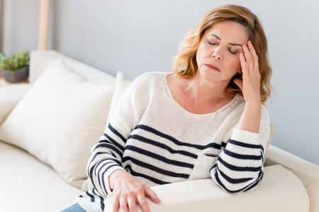 Mature woman is suffering from headache. She is sitting on sofa and touching temple. Her eyes are closed with frustration