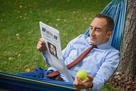 people relax: Successful businessman having rest on hammock in park. He is reading newspaper and smiling. Worker is holding ball
