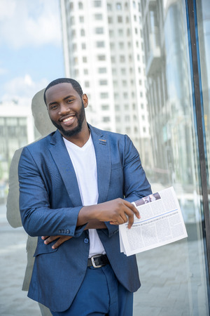 cross street with care: Cheerful African businessman is resting after work. He is standing and holding newspaper. Man is looking at camera and smiling Stock Photo