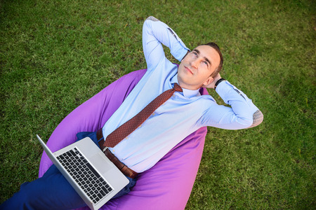 hands behind head: Businessman is relaxing in the nature. He is sitting on air chair with hands behind head. Man is holding laptop