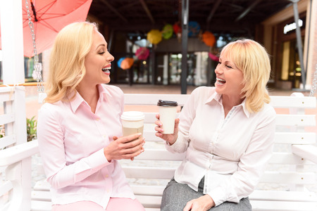 mother on bench: Cheerful young daughter is talking with her mother. They are sitting on bench and drinking coffee. Women are laughing