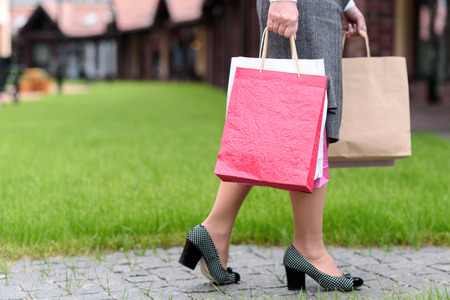 packets: Close up of fashionable woman going on street with shop packets Stock Photo