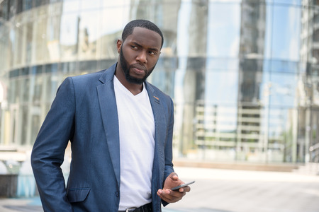 black business men: Serious young man is looking around with suspicion. He is standing near modern building and using mobile phone