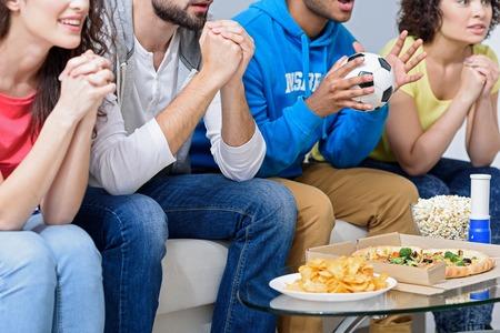 Wir müssen gewinnen. Nahaufnahme von aufgeregten Gruppe von Menschen beobachten Fußball zu Hause, sitzen auf Sofa in Zeile Standard-Bild - 60369322