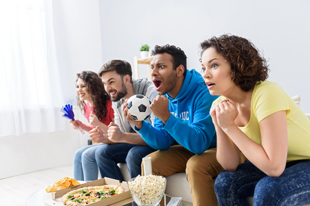 hurray: Worrying together. Group of friends sitting on sofa in row at home, watching TV together their favorite game