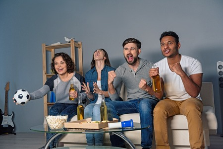 rooting: So strong emotions. Four football fans rooting for their soccer team on TV and sitting on white sofa at home