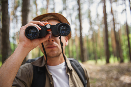 seriousness: Young tourist is lost in forest. He is standing and looking into the binoculars with seriousness
