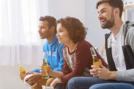cheering fans: Drinks and sports with friends. Cropped photo of football fans cheering on sofa with beers on sofa, sitting in row