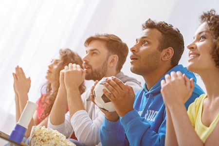 football teams: Let have another round. Close up of african man holding soccer ball in his hands and supporting football on TV with friends Stock Photo