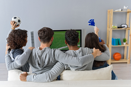 feeling good: Feeling good about their chances. Rear view of friends cheering match of their favorite team with soccer attributes