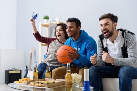 Basketball fans at home. Cheerful young friends watching TV and holding basketball ball while gesturing on couch at home Stock Photo