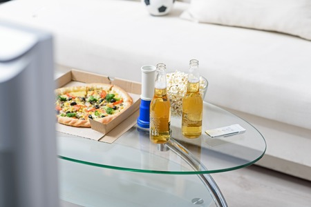 big game: On eve of big game. Top view of two bottles of beer standing on coffee table next to pizza, popcorn with white sofa in background Stock Photo