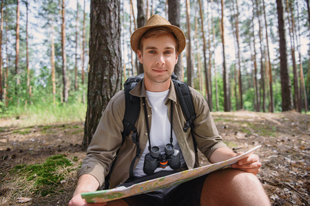 adventurer: Smart young adventurer is ready to travel. He is sitting and holding map. Man is looking at camera and smiling