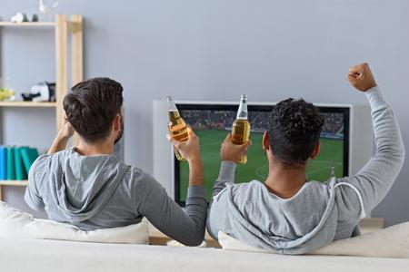Drankjes en sporten met een vriend. Achter mening van gelukkige mannelijke vrienden met bier tv kijken thuis, zittend op de bank Stockfoto