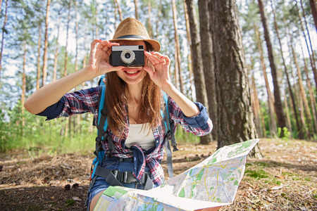 Carefree young tourist is taking photos of nature in forest. She is holding map and sitting. Woman is smiling with happiness Stock Photo