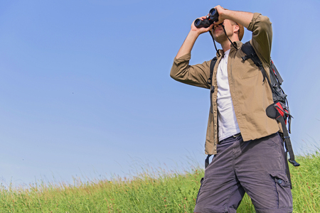 seriousness: Cheerful man is looking for place of destination with seriousness. He is standing on grass and using binoculars. Traveler is carrying touristic rucksack