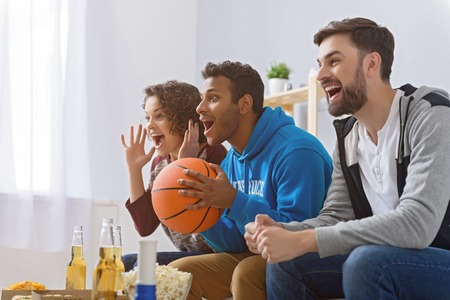 Good result of basketball match. Happy group of basketball fans watching sport tv with beer and pizza, sitting in row Stock Photo