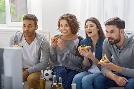 Lekker en leuk. Geschoten van gelukkige vrienden die pizza, bier drinken en op TV op bank thuis met venster op achtergrond letten op