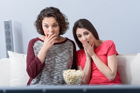 Absolutely shocked. Shot of two young girls sitting on their living room sofa and watching movie, eating popcorn Stock Photo