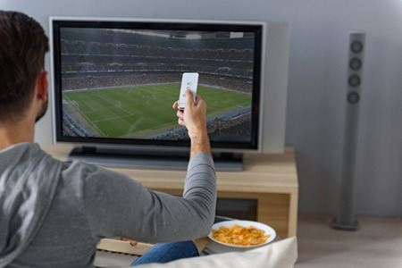 switching: Choosing favorite channel. Close up of man sitting back and holding remote, switching channel on football game