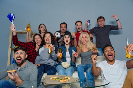 fanatic: Their favorite game is on. Group of friends fanatic football fans watching soccer game on television and celebrating goal on couch, isolated on grey background
